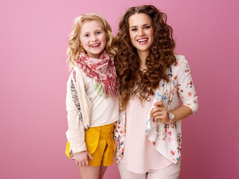 Gelukkige modieuze die moeder en dochter op roze achtergrond wordt geïsoleerd stock afbeelding