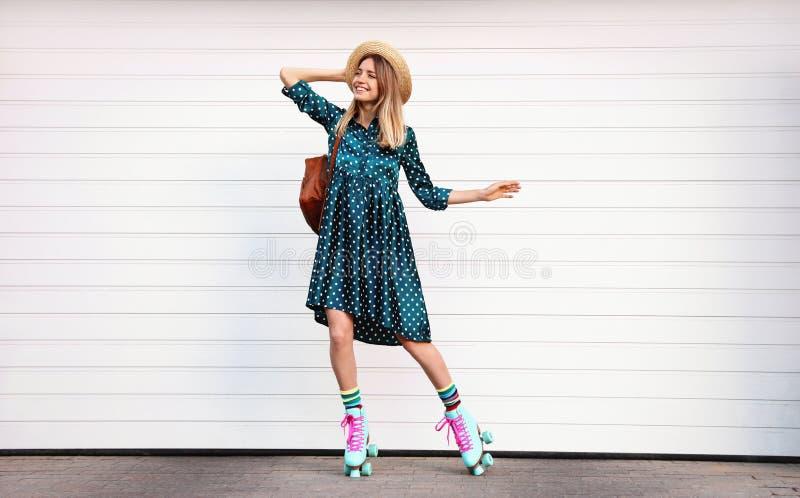 Gelukkige modieuze jonge vrouw met uitstekende rolschaatsen, hoed en rugzak dichtbij witte garagedeur royalty-vrije stock fotografie
