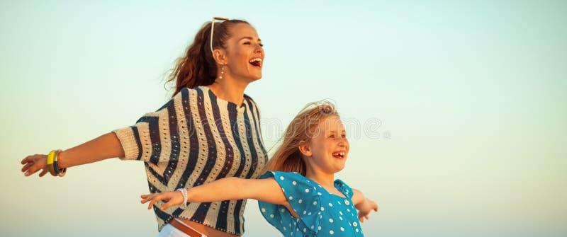 Gelukkige modieuze moeder en dochter op strand bij zich zonsondergang het verheugen royalty-vrije stock afbeeldingen