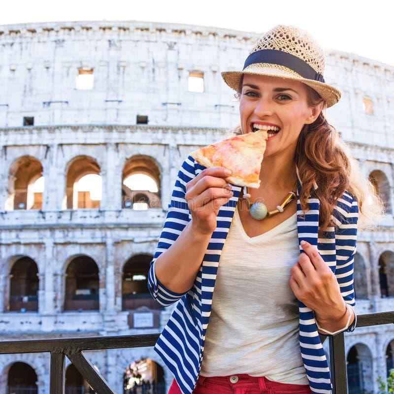 Gelukkige modieuze toeristenvrouw die in Rome, Italië pizza eten stock foto