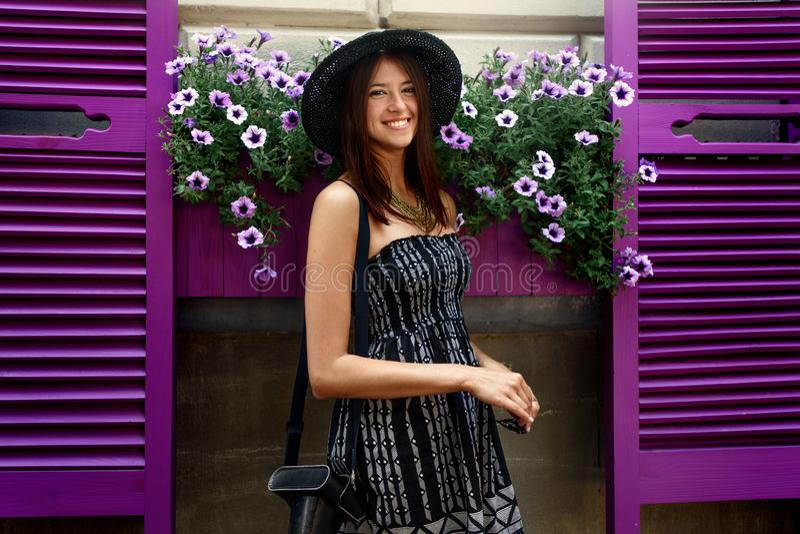 Gelukkige modieuze vrouw die hipster zich bij kleurrijke koffie met flowe bevinden royalty-vrije stock afbeeldingen