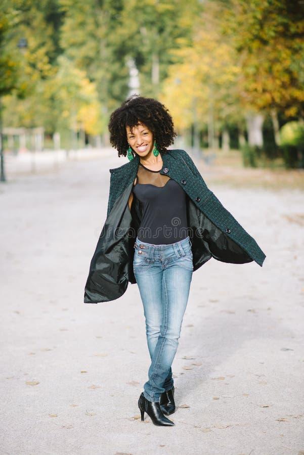 Gelukkige modieuze vrouw met afrohaar openlucht bij het park royalty-vrije stock afbeelding