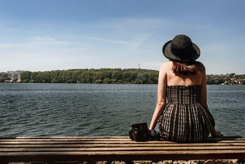 Gelukkige modieuze vrouwen hipster zitting op houten bank bij zonnige sho stock afbeelding