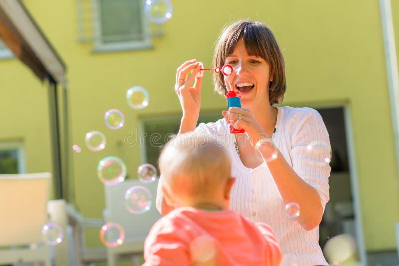 Gelukkige moeder blazende bellen voor haar baby royalty-vrije stock afbeeldingen