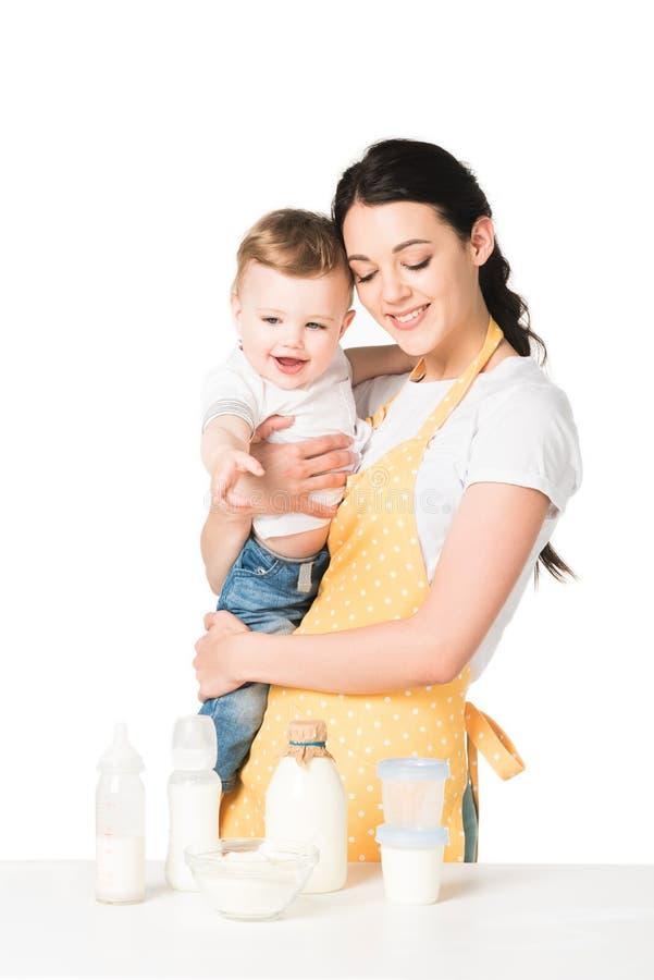gelukkige moeder in de babyjongen van de schortholding bij lijst met kinderenvoedsel stock fotografie