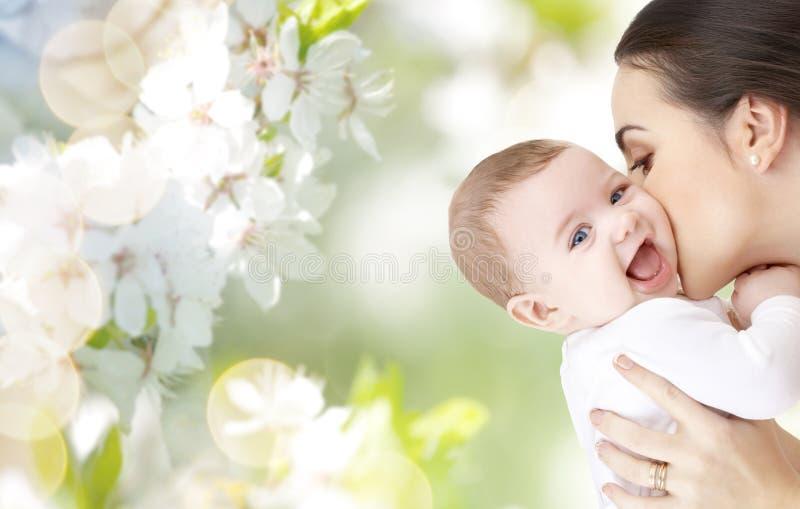Gelukkige moeder die aanbiddelijke baby kussen stock afbeeldingen