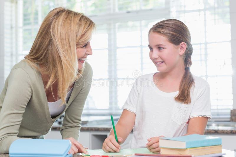 Gelukkige moeder die dochter helpen die thuiswerk doen stock afbeelding