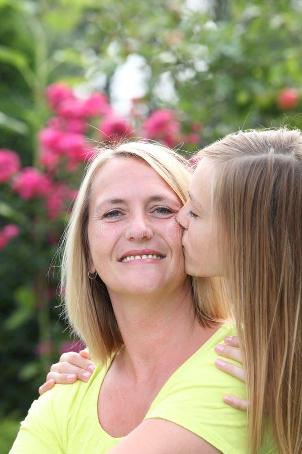 Gelukkige moeder die door haar dochter worden gekust royalty-vrije stock foto's