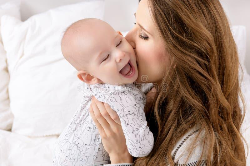 Gelukkige moeder die haar aanbiddelijke babyzoon kussen Gelukkige Familie Moeder en het pasgeboren kind spelen stock foto