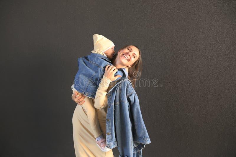 Gelukkige moeder die haar baby in modieuze kleren op een grijze achtergrond koesteren royalty-vrije stock fotografie