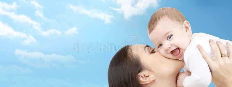 Gelukkige moeder die haar baby over blauwe hemel kussen stock afbeelding