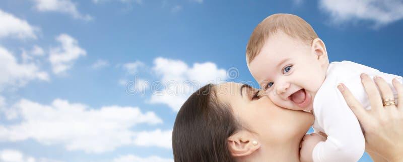 Gelukkige moeder die haar baby over blauwe hemel kussen royalty-vrije stock afbeeldingen