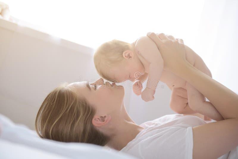 Gelukkige moeder die haar babymeisje steunen royalty-vrije stock foto's
