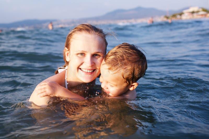 Gelukkige moeder die haar jonge zoon onderwijzen om te zwemmen royalty-vrije stock fotografie