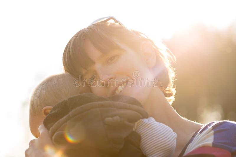 Gelukkige moeder die haar jonge zuigeling knuffelen royalty-vrije stock afbeelding