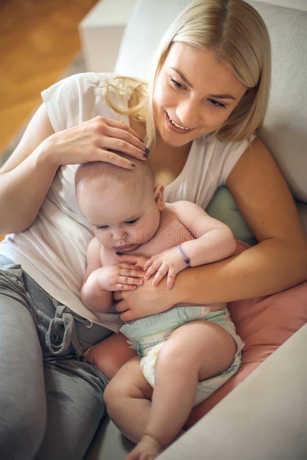 Gelukkige moeder die haar thuis houden weinig babyjongen in wapens royalty-vrije stock fotografie
