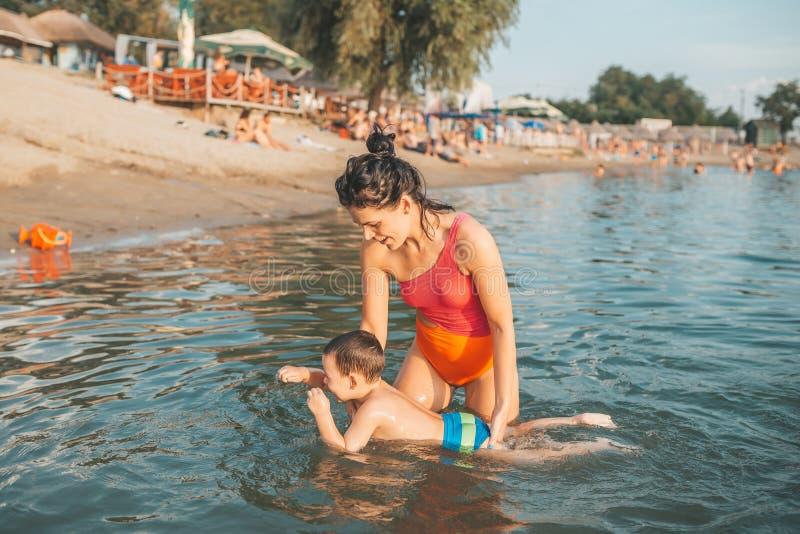 Gelukkige moeder die haar weinig zoon onderwijzen die in het water, op het strand zwemmen royalty-vrije stock afbeeldingen