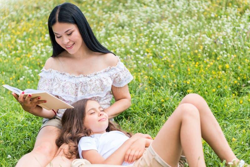 Gelukkige moeder die interessant verhaal vertellen aan haar dromerig kind stock fotografie