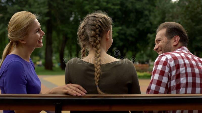 Gelukkige moeder die met dochter en echtgenoot in park, het gekscheren en het lachen spreken stock fotografie