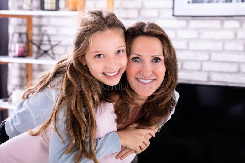 Gelukkige Moeder die op de rug aan Haar Dochter geven royalty-vrije stock fotografie