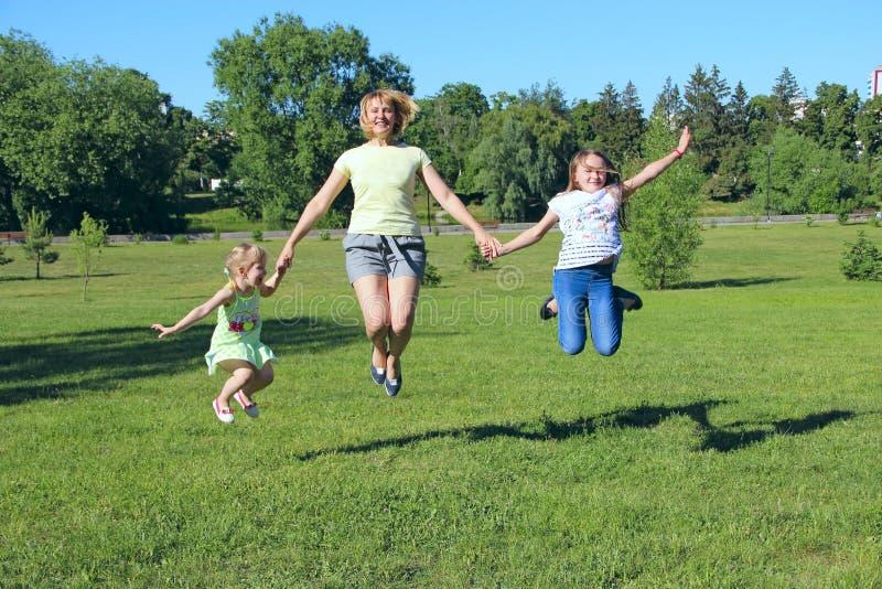 Gelukkige moeder die pret hebben die met haar dochters op groen gras springen royalty-vrije stock foto