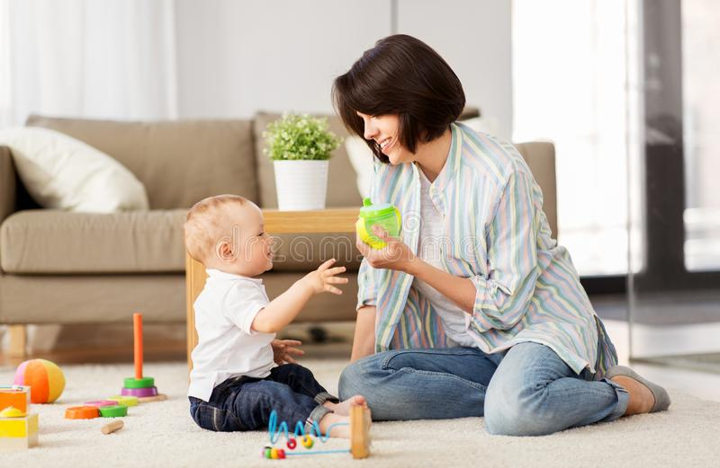 Gelukkige moeder die sippy kop thuis geven aan babyzoon stock foto