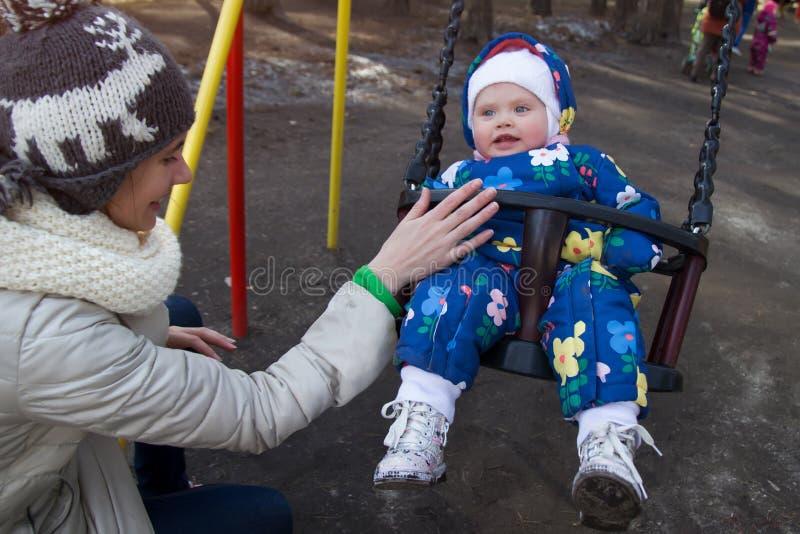Gelukkige moeder duwende lachende blauw-eyed dochter op schommeling in een de lentepark royalty-vrije stock afbeeldingen