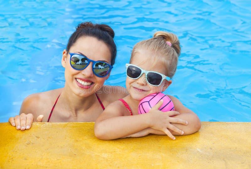 Gelukkige moeder en aanbiddelijk weinig dochter die pret in een swimmi hebben royalty-vrije stock afbeelding