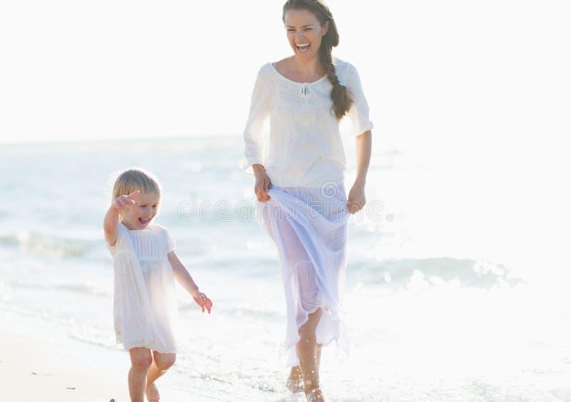 Gelukkige moeder en baby die langs overzeese kust lopen stock afbeelding