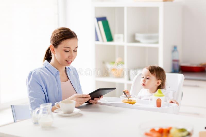 Gelukkige moeder en baby die ontbijt hebben thuis stock foto's