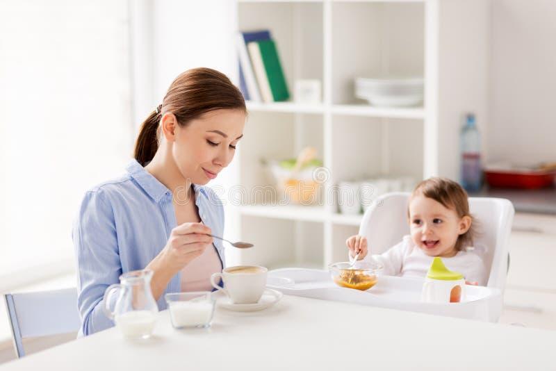 Gelukkige moeder en baby die ontbijt hebben thuis royalty-vrije stock fotografie