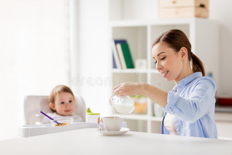 Gelukkige moeder en baby die ontbijt hebben thuis stock foto