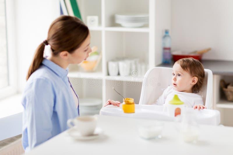 Gelukkige moeder en baby die ontbijt hebben thuis stock afbeeldingen