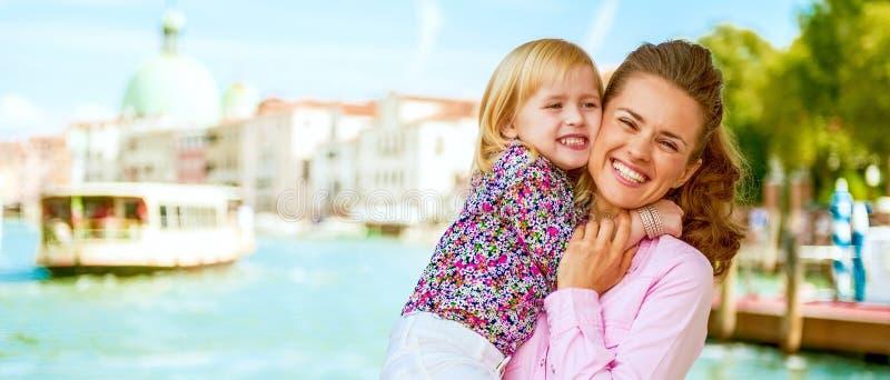 Gelukkige moeder en baby die op groot kanaal koesteren embankm stock foto