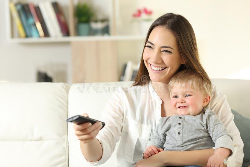 Gelukkige moeder en baby die op TV thuis letten stock foto