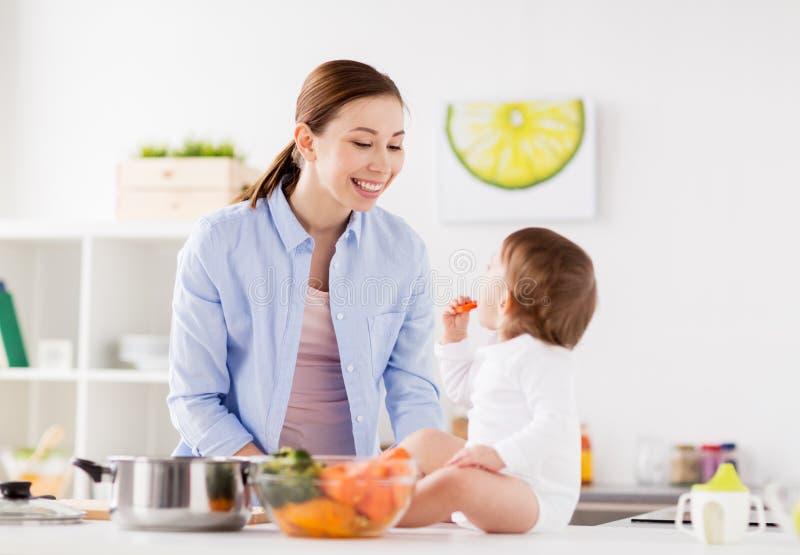 Gelukkige moeder en baby die thuis keuken eten royalty-vrije stock fotografie