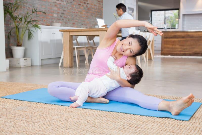 Gelukkige moeder en babydochter die op mat uitoefenen stock foto's