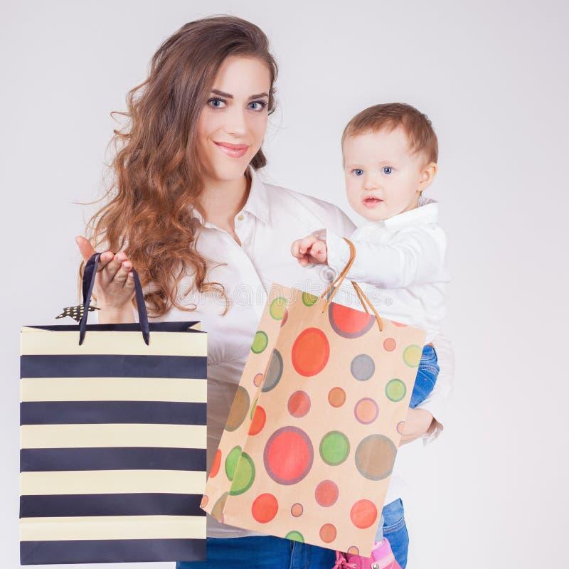 Gelukkige moeder en de grappige zakken van de babyholding met aankopen stock fotografie