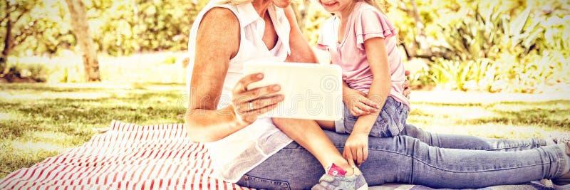 Gelukkige moeder en dochter die digitale tablet in park gebruiken royalty-vrije stock foto's