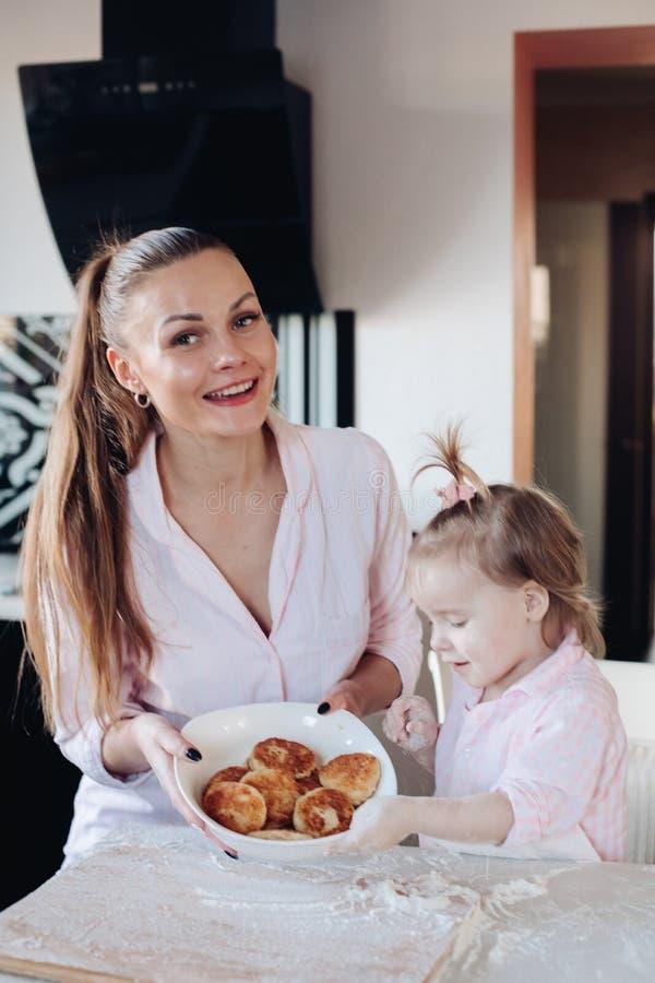Gelukkige moeder en dochter die gebakken gestremde melkfritter tonen royalty-vrije stock afbeeldingen