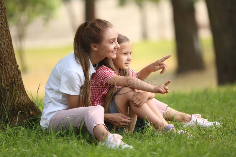 Gelukkige moeder en dochter die in groen park rusten royalty-vrije stock foto's