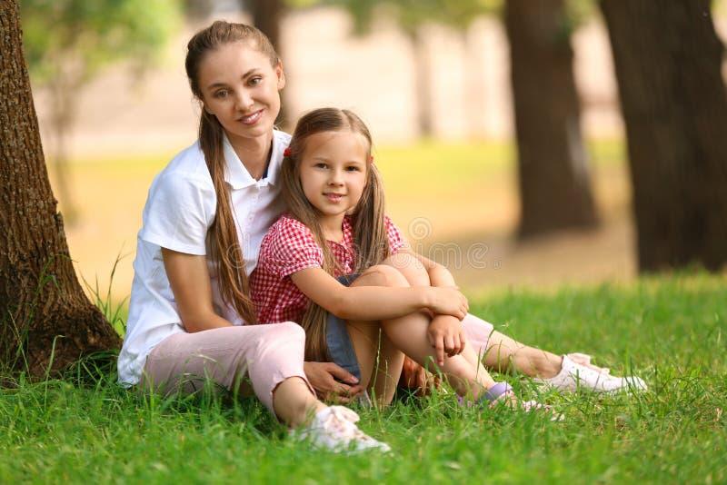 Gelukkige moeder en dochter die in groen park rusten royalty-vrije stock foto