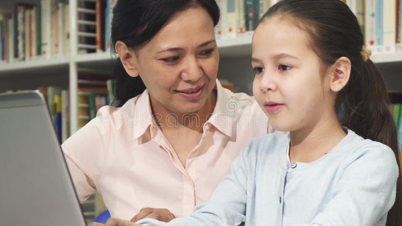 Gelukkige moeder en dochter die laptop met behulp van terwijl het bestuderen royalty-vrije stock fotografie