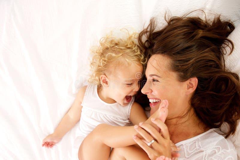 Gelukkige moeder en dochter die op bed liggen royalty-vrije stock foto