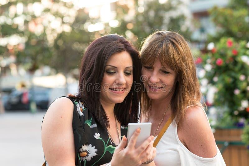Gelukkige moeder en dochter die op mobiele telefoon buiten letten stock foto's