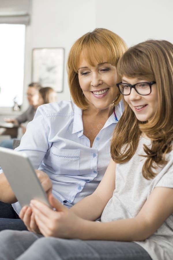 Gelukkige moeder en dochter die tabletpc met familiezitting thuis met behulp van op achtergrond stock fotografie