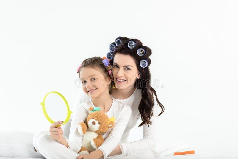 Gelukkige moeder en dochter die terwijl het houden van handspiegel en teddybeer koesteren royalty-vrije stock foto