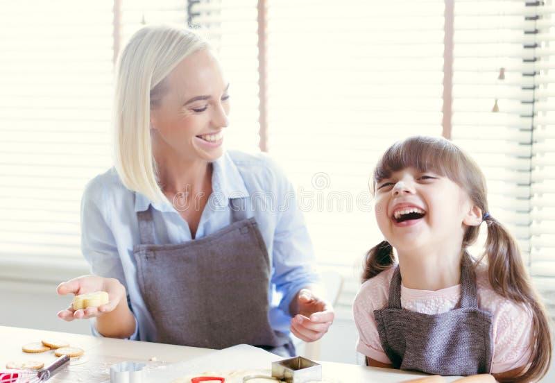 Gelukkige moeder en dochter die terwijl het kneden van het deeg lachen en royalty-vrije stock afbeelding