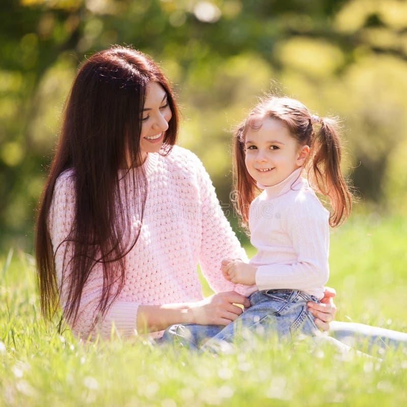 Gelukkige moeder en dochter in het de zomerpark De sc?ne van de schoonheidsaard met familie openluchtlevensstijl Gelukkige famili royalty-vrije stock foto