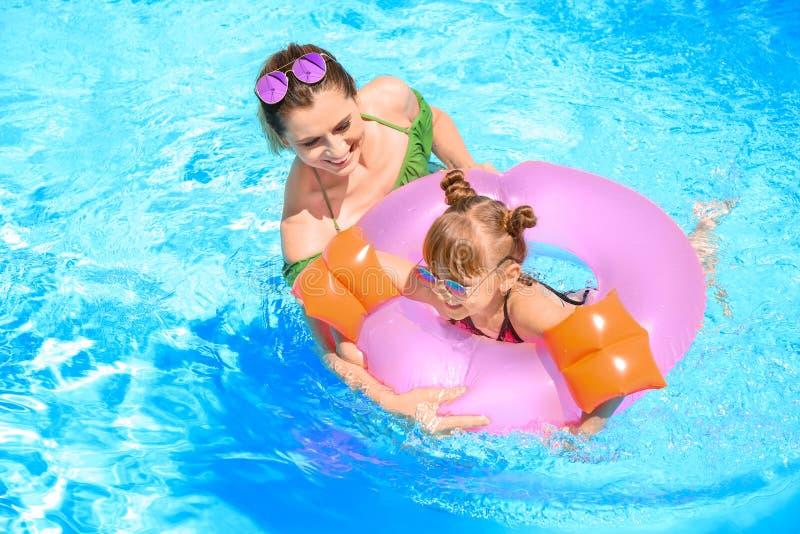 Gelukkige moeder en dochter met opblaasbare ring in zwembad stock afbeelding
